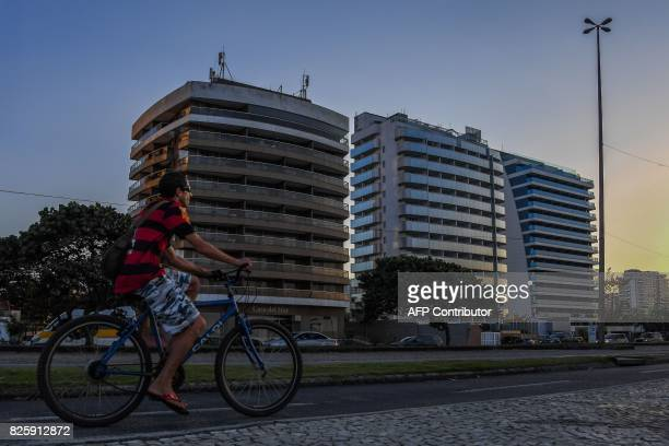 A man rides his bike in front of an hotel that became a residense after Rio 2016 Olympic Games on Praia da Barra in Rio de Janeiro on August 3 2017...