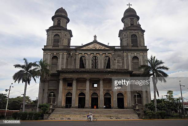 A man rides his bike in front of an old cathedral in Managua on October 19 2009 AFP PHOTO/Elmer Martinez / AFP PHOTO / ELMER MARTINEZ