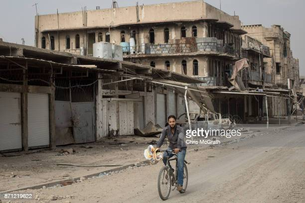 A man rides his bike in front of destroyed buildings in an outer neighborhood of the Old City in West Mosul on November 6 2017 in Mosul Iraq Five...