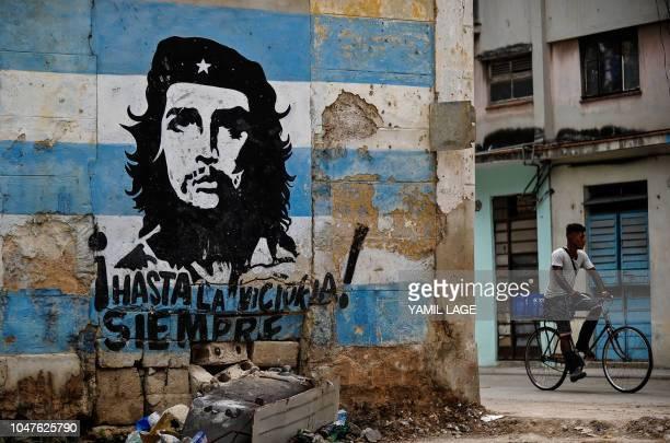 TOPSHOT A man rides his bike near a graffiti depicting Argentineborn revolutionary leader Ernesto Che Guevara in Havana ahead of the 51st anniversary...