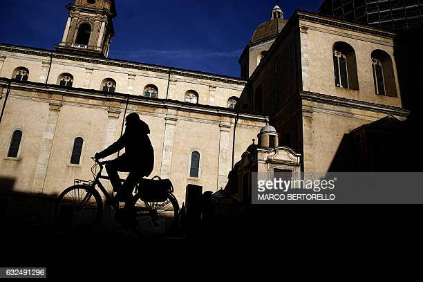 A man rides his bike near the Duomo on January 23 2017 in Turin / AFP / MARCO BERTORELLO