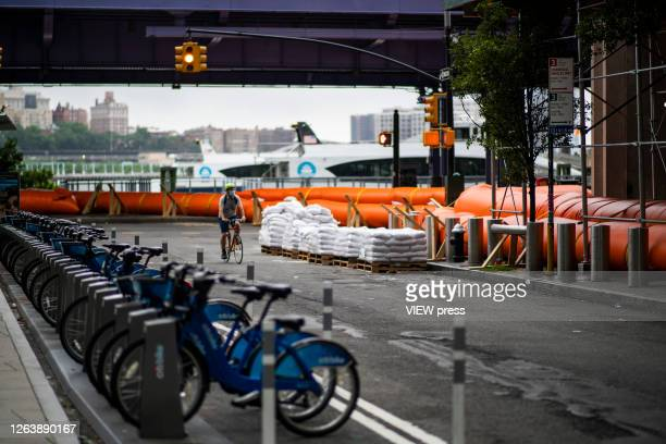 A man rides his bike next to flood barriers used to prevent flooding at the South Street Seaport as the city gets ready for tropical storm Isaias on...
