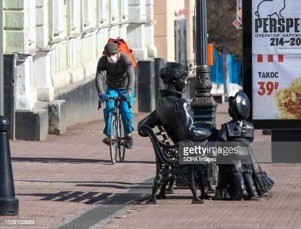 Man rides his bike on a deserted street wearing a face mask as a preventive measure, during the corona virus pandemic. People in Nizhny Novgorod are...