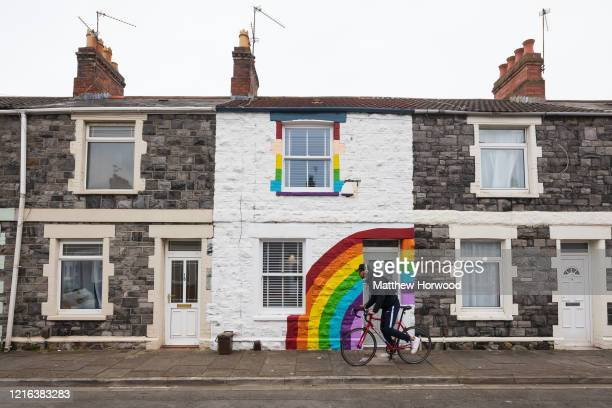 Man rides his bike passed a terraced house painted with a rainbow in support of the National Health Service on Gwendoline Street in Splott on April 2...