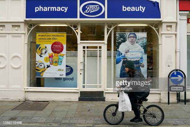 A man rides his bike past a Boots pharmacy on July 09 2020 in York United Kingdom Many UK businesses are announcing job losses due to the effects of...