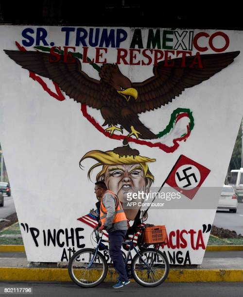 A man rides his bike past a graffiti painted against US President Donald Trump in Mexico City on June 27 2017 / AFP PHOTO / ALFREDO ESTRELLA