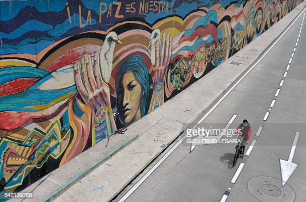 A man rides his bike past a graffiti with a sentence that reads Peace is ours in Bogota on June 22 2016 Colombia's government and the FARC guerrilla...