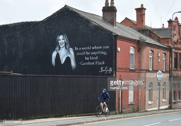 Man rides his bike past a mural by Artists Scott Wilcock which pays tribute to TV star Caroline Flack on February 21, 2021 in Wigan, England. Ms...