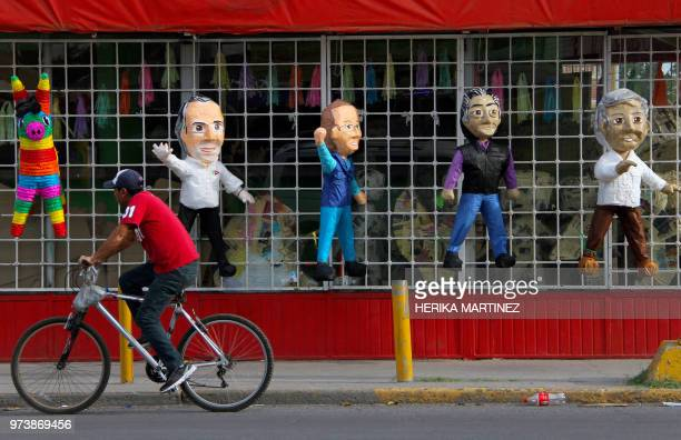 A man rides his bike past pinatas depicting Mexican presidential candidates Jose Antonio Meade Ricardo Anaya independent Jaime 'el Bronco' Rodriguez...