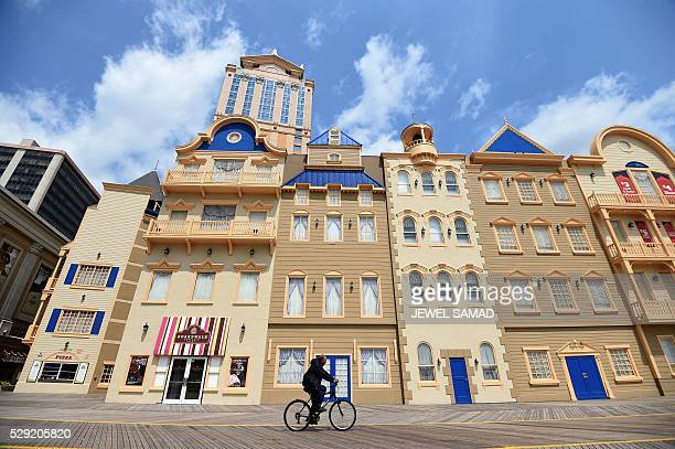 A man rides his bike past stores on the boardwalk in Atlantic City New Jersey on May 8 2016 Atlantic City the famous US gambling resort town and...