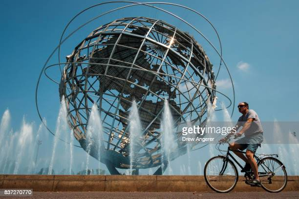 Man rides his bike past the fountains at the Unisphere steel structure at Flushing Meadows-Corona Park, August 22, 2017 in the Queens borough of New...