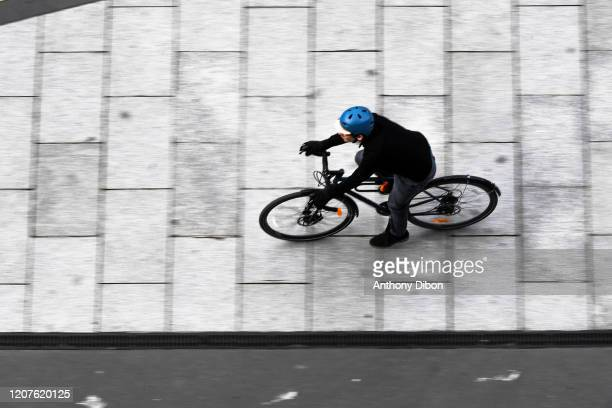 Man rides his bike . People of the city came out of their houses to enjoy and play sports on March 18, 2020 in Paris, France.