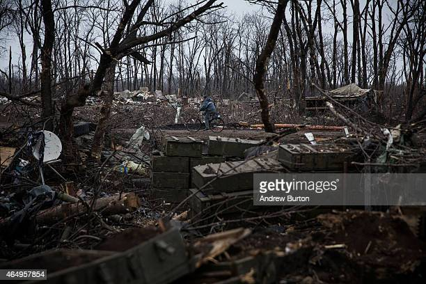 Man rides his bike through a desimated battlefield where the Ukrainian army was defeated by pro-Russian rebels on March 2, 2015 on the outskirts of...