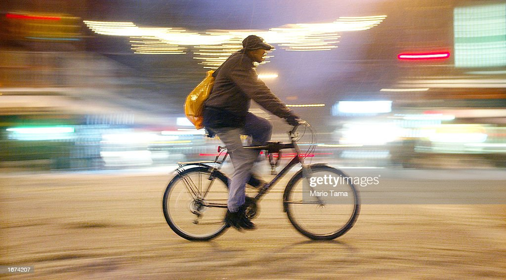 A man rides his bike through the snow down Third Avenue December 5, 2002 in New York City. The city is expected to get as many as six inches of snow by the end of the day.
