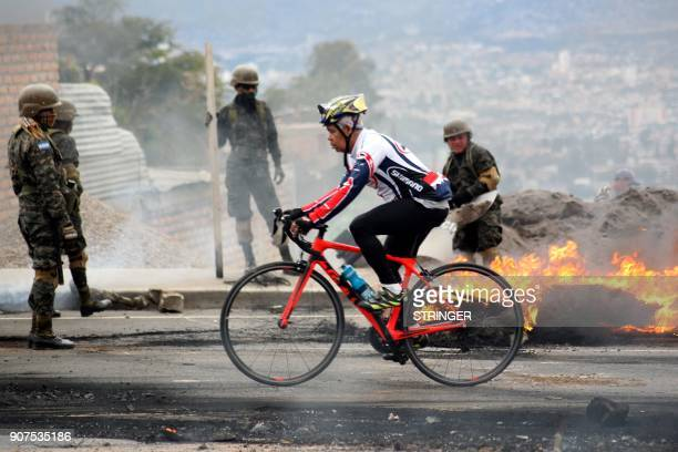 TOPSHOT A man rides his bike while riot police and soldiers try to remove burnt tires after clashes with supporters of the Honduran Opposition...