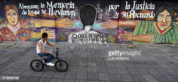 A man rides his bikes next to a mural reading We embrace the memory of those who were taken for justice and memory From 1982 to 2012000 victims of...