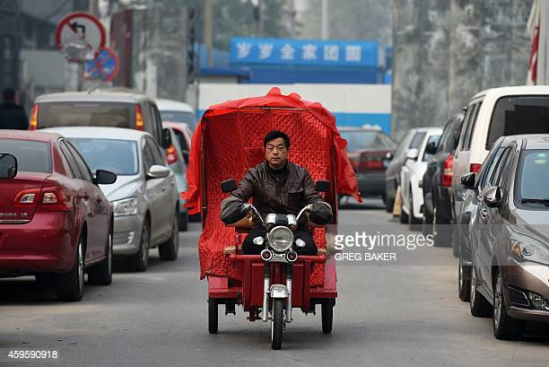 A man rides his covered electric tricycle taxi on a polluted day in Beijing on November 26 2014 China said on November 25 that developed countries...