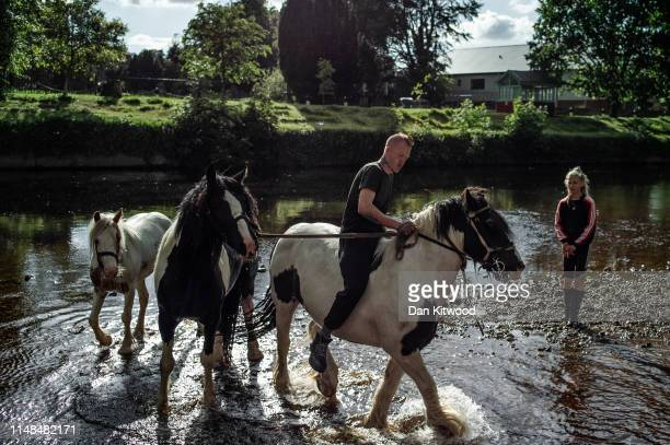Man rides his horses in the River Eden during the annual Appleby Horse Fair on June 06, 2019 in Appleby-in-Westmorland, England. The annual gathering...