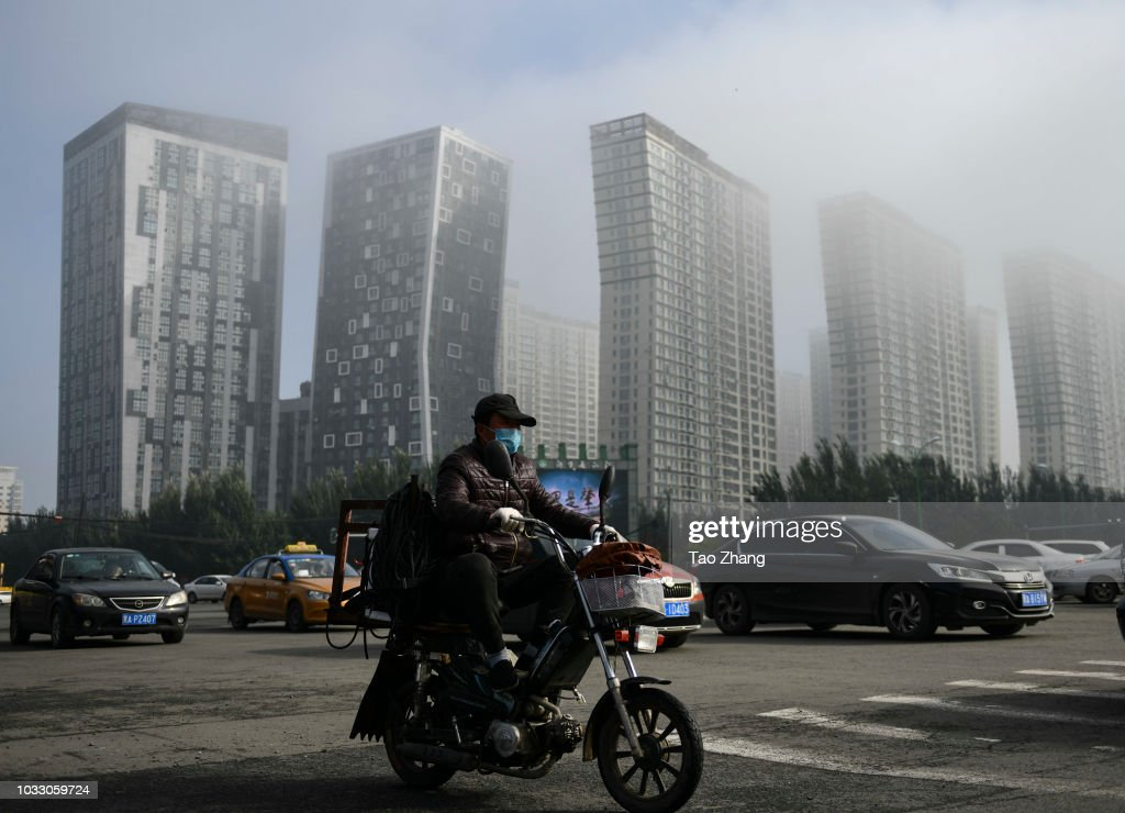 A man rides his motorbike at the Changjiang street during dense fog enveloping Harbin on September 14, 2018 in Harbin, China. The meteorological department issued a yellow alert for dense fog