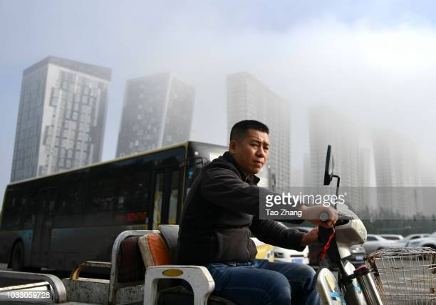 A man rides his motorbike at the Changjiang street during dense fog enveloping Harbin on September 14 2018 in Harbin China The meteorological...