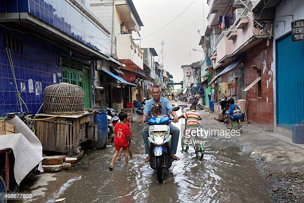A man rides his motorbike down a flooded street in the Maura Baru district November 24 2015 in Jakarta Indonesia Jakarta Southeast Asia's largest...