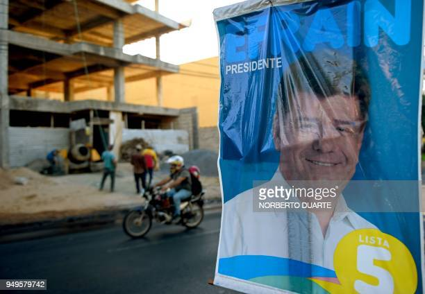 A man rides his motorbike past a poster of Paraguay's presidential candidate for the National Alliance Efrain Alegre in Asuncion on April 21 on the...