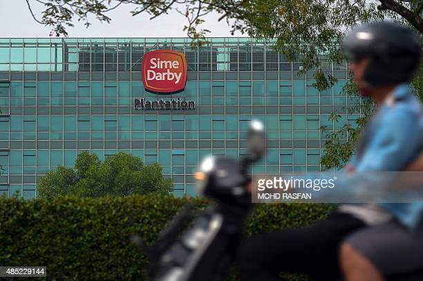 A man rides his motorbike pasts the logo of Malaysian company Sime Darby at their plantation office in Subang on the outskirts of Kuala Lumpur on...