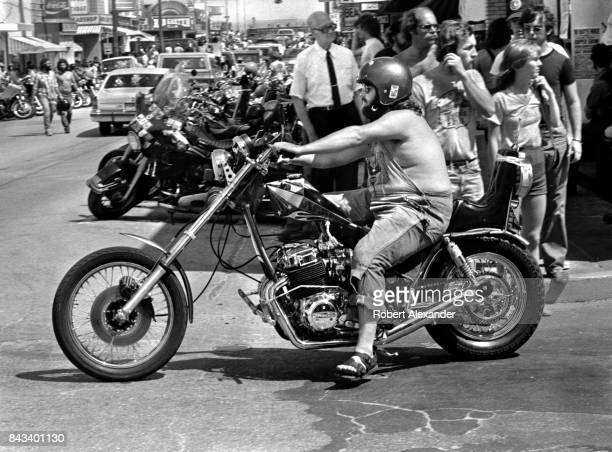 A man rides his motorcycle along a street in Daytona Beach Florida during the city's 1983 Bike Week The annual motorcycle event and rally has...