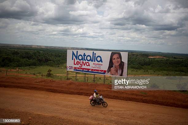 Man rides his motorcycle past a billboard with propaganda of a mayoral candidate for the upcoming elections, on the outskirts of Puerto Gaitan, Meta...