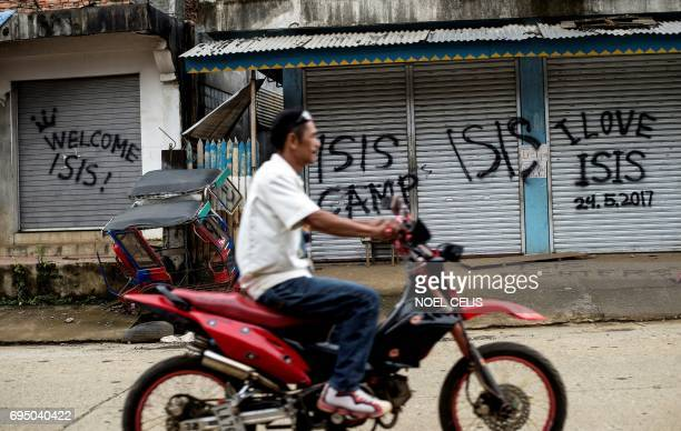 A man rides his motorcycle past shuttered shopfronts sprayed with proIslamic State group grafitti in Marawi on the southern island of Mindanao on...