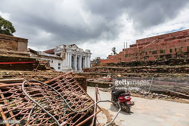 Man rides his motorcycle past the UNESCO heritage listed site of Durbar Square in the heart of Kathmandu on July 25, 29015. Today marks the 3 month...