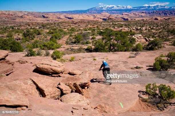 un hombre monta su bicicleta de montaña por un sendero a campo traviesa en un día soleado en moab, utah, usa. - cross country cycling fotografías e imágenes de stock