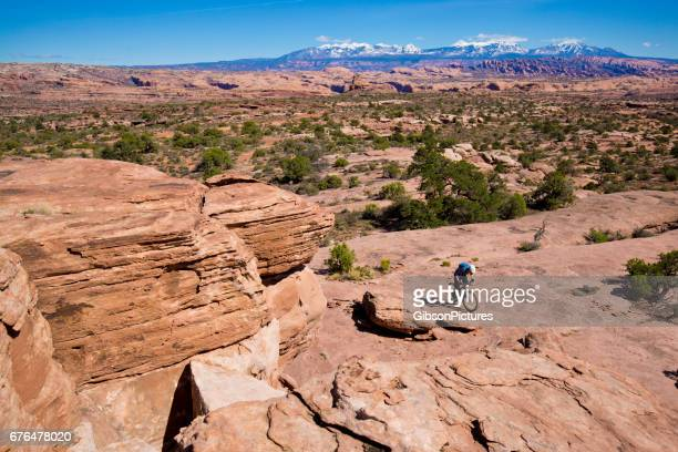 A man rides his mountain bike on a cross-country trail in Moab, Utah, USA.