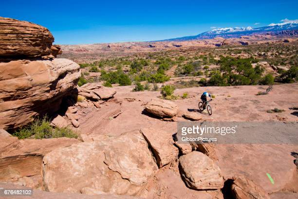 a man rides his mountain bike on a cross-country trail in moab, utah, usa. - cross country cycling stock photos and pictures