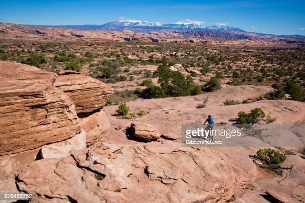 a man rides his mountain bike on a cross-country trail in moab, utah, usa on a sunny day. - moab utah stock photos and pictures