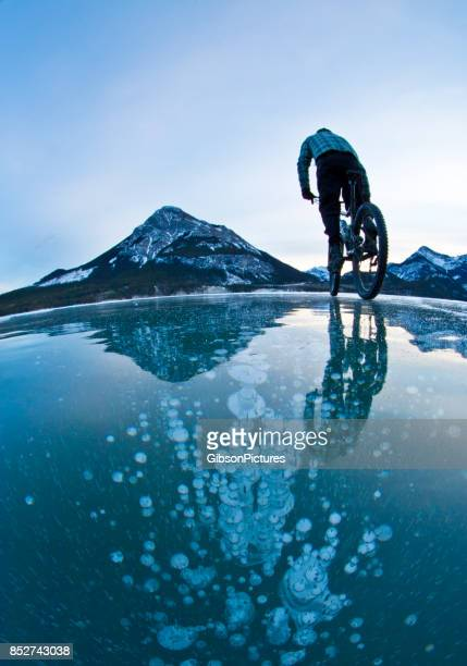 A man rides his mountain bike over the frozen methane bubbles in the ice of a lake in the Rocky Mountains of Alberta, Canada in the wintertime.