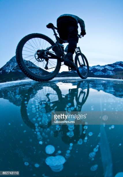 Un hombre monta su bicicleta de montaña sobre las burbujas de metano congelado en el hielo de un lago en las montañas rocosas de Alberta, Canadá en el invierno.