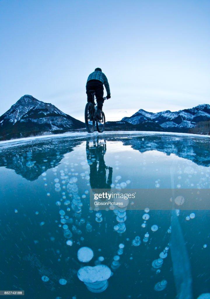 Un hombre monta su bicicleta de montaña sobre las burbujas de metano congelado en el hielo de un lago en las montañas rocosas de Alberta, Canadá en el invierno. : Foto de stock