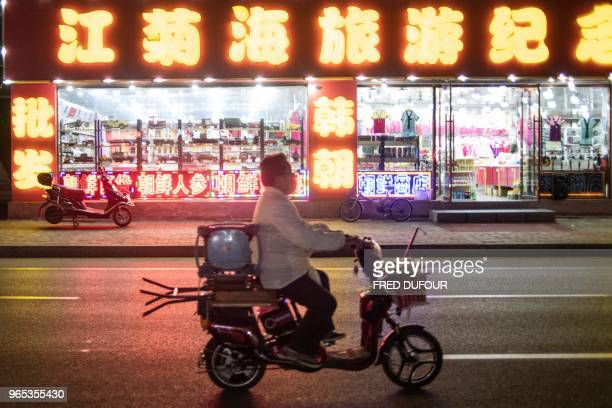 A man rides his scooter near a tourist shop in the Chinese border town of Dandong in China's northeast Liaoning province on May 30 2018 The city of...