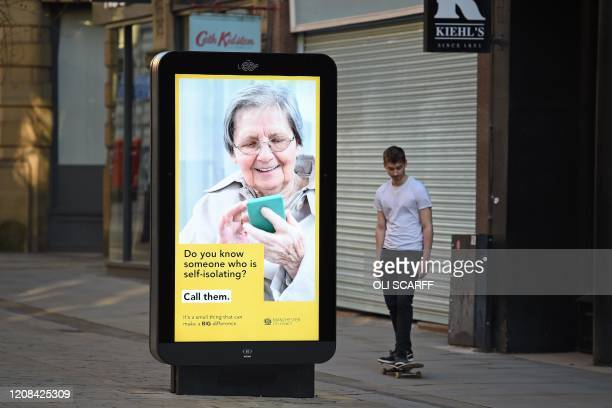A man rides his skateboard past a poster encouraging people to contact those who are selfisolating in a near deserted central Manchester north west...