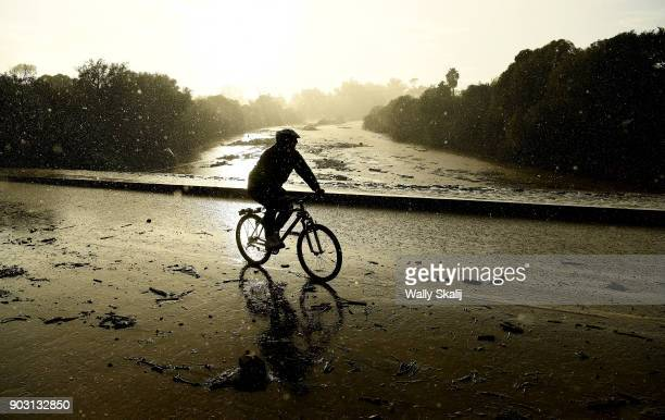 A man rides hus bike in the rain on Olive Mill Road above the flooded 101 freeway in Montecito after a major storm hit the burn area Tuesday January...