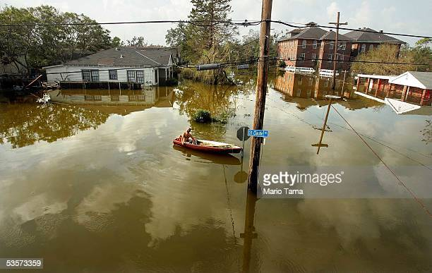 Man rides in a canoe in high water after Hurricane Katrina devastated the area August 31, 2005 in New Orleans, Louisiana. Devastation is widespread...