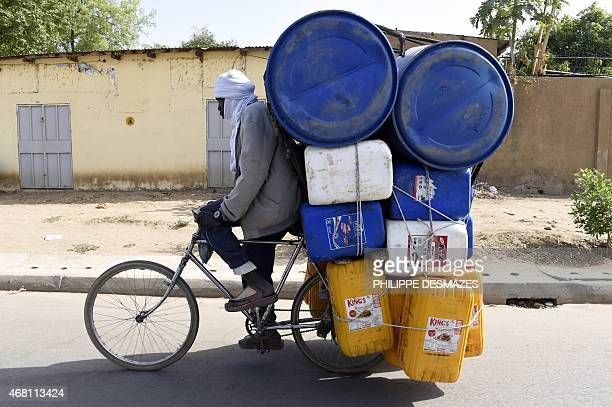 A man rides on a bicycle loaded with containers in N'Djamena on March 30 2015 AFP PHOTO / PHILIPPE DESMAZES