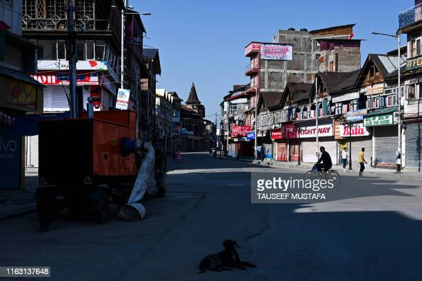 TOPSHOT A man rides on a bicycle near closed shops in Srinagar on August 22 2019