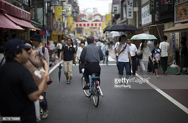 A man rides on a bicycle through a shopping street in the Sugamo district of Tokyo Japan on Monday Sept 19 2016 The proportion of Japan's aged has...