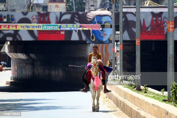 A man rides on a horse along a deserted street during the first day of a 21day governmentimposed nationwide lockdown as a preventive measure against...