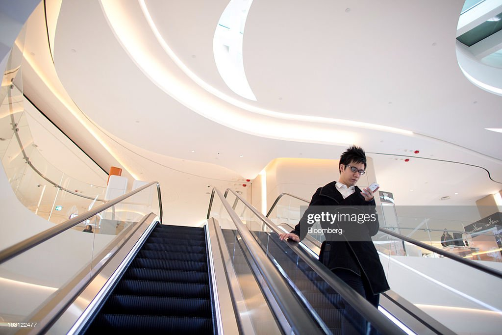 A man rides on an escalator while looking at his mobile phone at Hysan Development Co.'s Hysan Place mall in the Causeway Bay district of Hong Kong, China, on Monday, March 4, 2013. Hysan is scheduled to release earnings on March 6. Photographer: Lam Yik Fei/Bloomberg via Getty Images