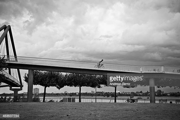 A man rides on his bicycle on a bridge at Duesseldorf media harbor on August 12 2014 in Duesseldorf Germany