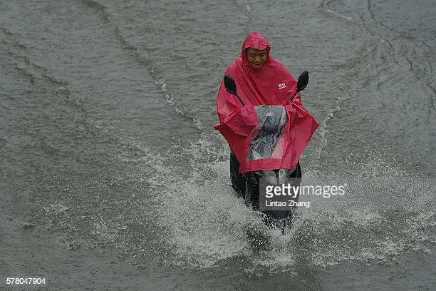 A man rides on the flooded street in the heavy rain on July 20 2016 in Beijing China Heavy rainfall hit capital Beijing and Beijing Meteorological...