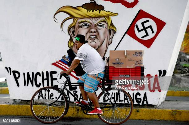A man rides past a graffiti painted against US President Donald Trump in Mexico City on June 27 2017 / AFP PHOTO / ALFREDO ESTRELLA